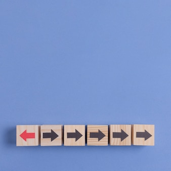 青い空間の背景に矢印の付いた木製キューブ