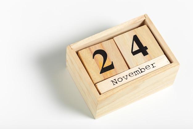 Деревянные кубики с датой на белом фоне. 24 ноября