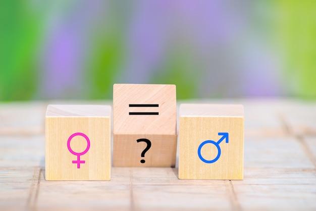 Деревянные кубики с символами феминизма и маскулизма, вопросительным знаком и знаком равенства. гендер, половое равенство. права человека.