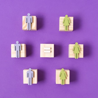 Wooden cubes with green women and blue men figurines equality concept