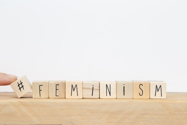 Wooden cubes with a hashtag and the word feminism, social media concept
