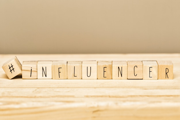 Wooden cubes with a hashtag and the word influencer