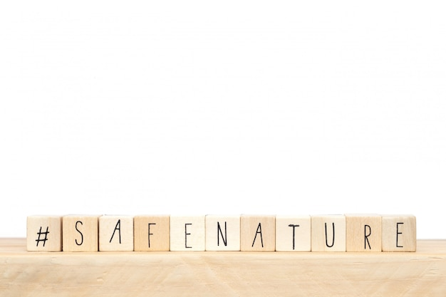 Wooden cubes with a hashtag and the words safe nature, social media concept,