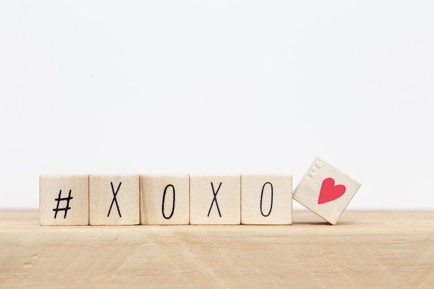 Wooden cubes with hashtag and xoxo hugs and kisses letters of love, social media concept