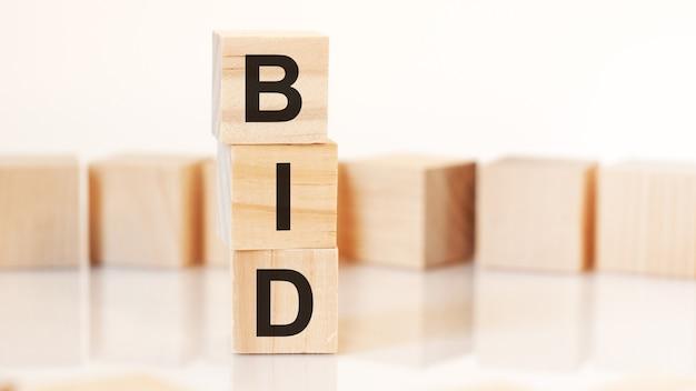 수직 피라미드에 배열된 bid 문자가 있는 나무 큐브, 흰색 배경, 테이블 표면에서 반사, 비즈니스 개념