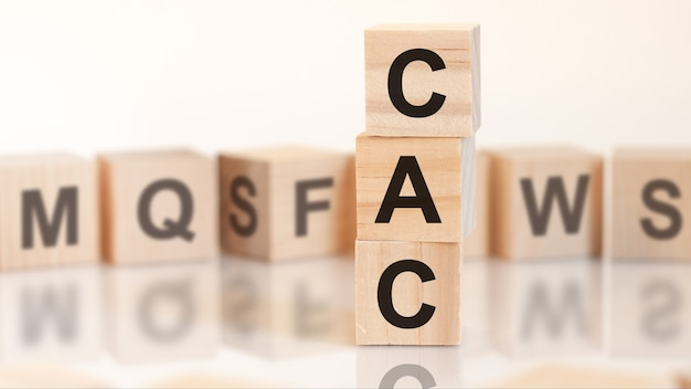 Wooden cubes with letters cac arranged in a vertical pyramid, on the light background, reflection surface, business concept. cac short for customer acquisition cost