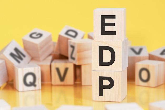 Edp라는 글자가 수직 피라미드에 배열된 나무 큐브, 노란색 배경, 테이블 표면에서 반사, 비즈니스 개념, edp - 전자 데이터 처리의 약자