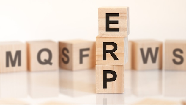 Wooden cubes with letters erp arranged in a vertical pyramid, white background, reflection from the surface of the table, business concept