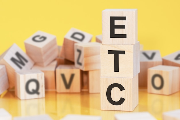 Wooden cubes with letters etc arranged in a vertical pyramid, yellow background, reflection from the surface of the table, business concept. etc - short for electronic trade confirmation
