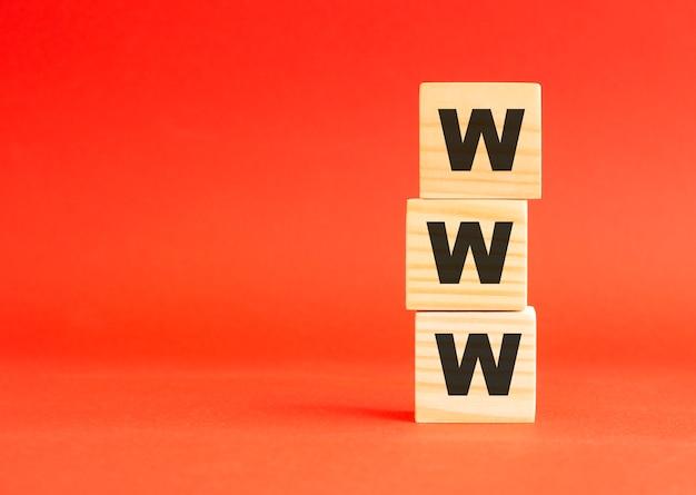 Деревянные кубики с буквами. для вашего дизайна. деревянные кубики на красной поверхности. слева свободное место.