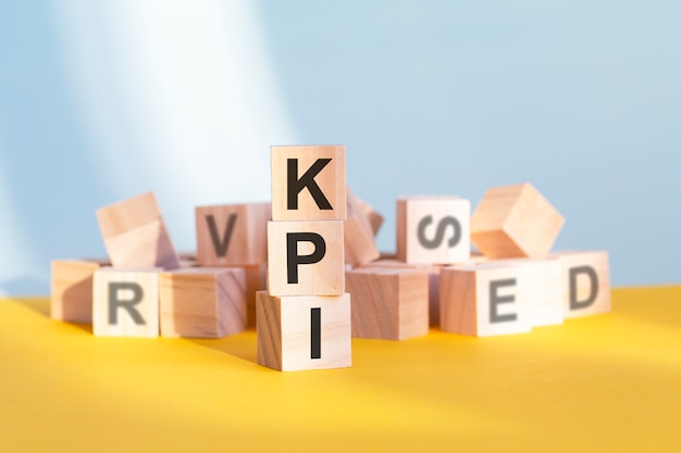 Wooden cubes with letters kpi arranged in a vertical pyramid, grey and yellow background, business concept. kpi - short for key performance indicators