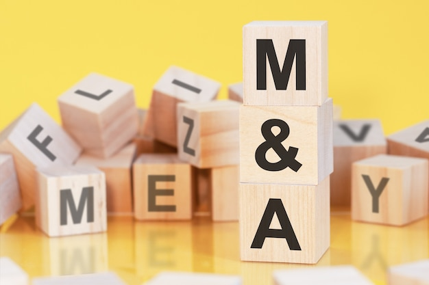 Wooden cubes with letters m and a arranged in a vertical pyramid, yellow background, reflection from the surface of the table, m and a - mergers and acquisitions