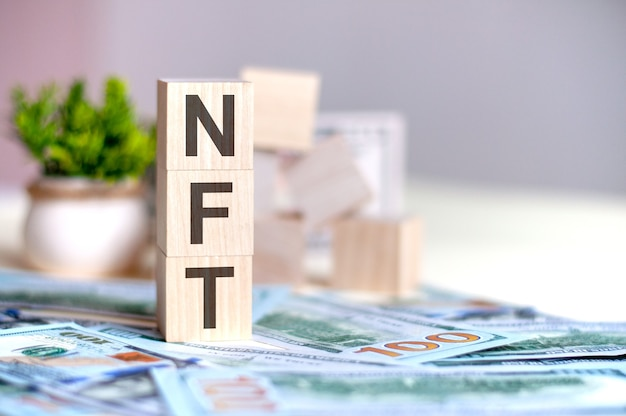 Wooden cubes with the letters nft arranged in a vertical pyramid on banknotes, green potted plant. nft - short for , business concept