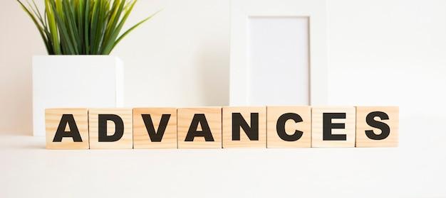 白いテーブルの上の文字と木製の立方体。言葉はadvancesです。白色の背景。