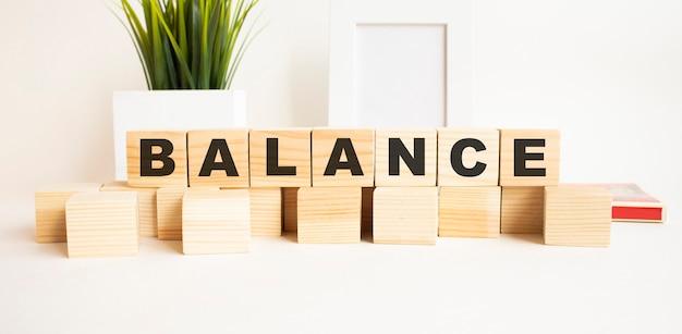Деревянные кубики с буквами на белом столе. слово баланс.