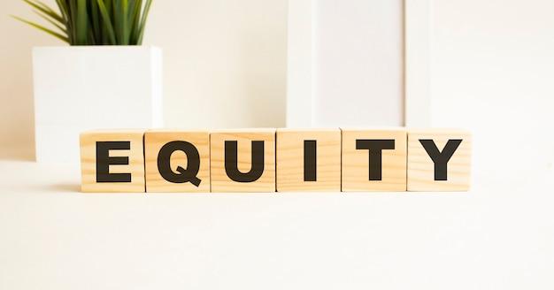 흰색 테이블에 글자와 나무 큐브. 단어는 equity입니다. 사진 프레임, 집 식물 흰색 배경입니다.