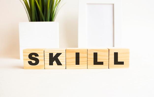 흰색 테이블에 글자와 나무 큐브. 단어는 skill입니다. 사진 프레임, 집 식물 흰색 배경입니다.