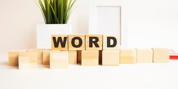 白いテーブルの上の文字と木製の立方体。言葉はwordです。フォトフレーム、観葉植物と白い背景。