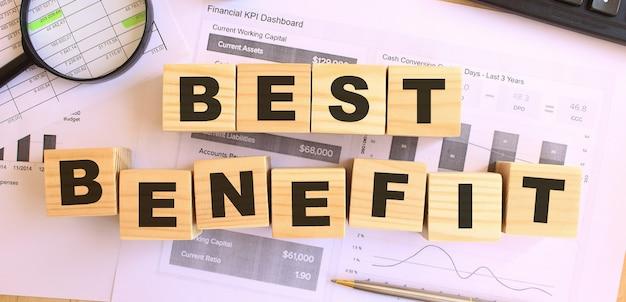 사무실에있는 테이블에 편지와 함께 나무 큐브. best benefit라고 문자 메시지를 보내세요. 금융 개념.