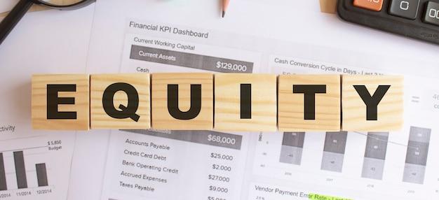 Деревянные кубики с буквами на столе в офисе. текст equity. финансовая концепция.