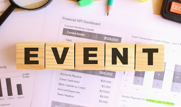 オフィスのテーブルに文字が書かれた木製の立方体。テキストイベント。財務コンセプト。