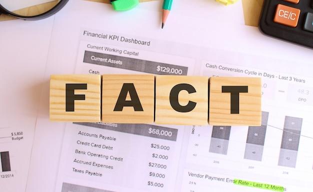 사무실에있는 테이블에 편지와 함께 나무 큐브. fact 문자. 금융 개념.