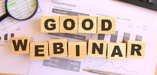 オフィスのテーブルに文字が書かれた木製の立方体。 goodwebinarにテキストメッセージを送信します。財務コンセプト。