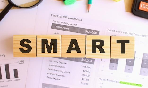 オフィスのテーブルに文字が書かれた木製の立方体。 smartにテキストメッセージを送信します。財務コンセプト。