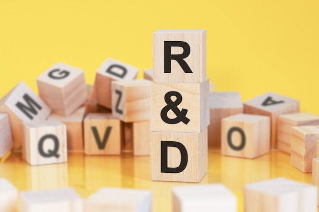 Wooden cubes with letters q and a arranged in a vertical pyramid, yellow background, reflection from the surface of the table, business concept, q and a - short for question and answer