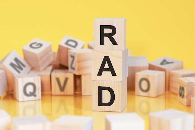 Деревянные кубики с буквами rad, расположенными в вертикальной пирамиде, желтый фон, отражение от поверхности стола, бизнес-концепция, rad - сокращение от быстрой разработки приложений.