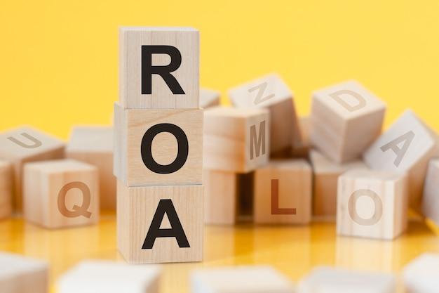 테이블, 비즈니스 개념, roa의 표면에서 수직 피라미드 반사로 배열 된 문자 roa가있는 나무 큐브-자산 수익률의 약자