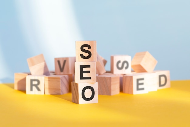 Wooden cubes with letters seo arranged in a vertical pyramid, yellow background, reflection from the surface of the table, business concept. seo - short for search engines optimization