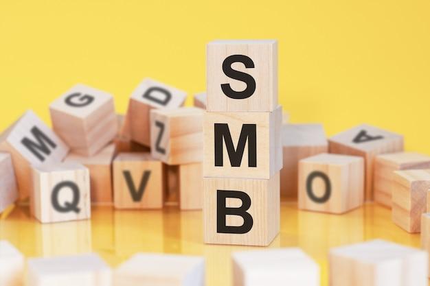 수직 피라미드, 노란색 배경, 테이블, 비즈니스 개념의 표면에서 반사에 배열 된 문자 smb와 나무 큐브. smb-서버 메시지 블록의 약자