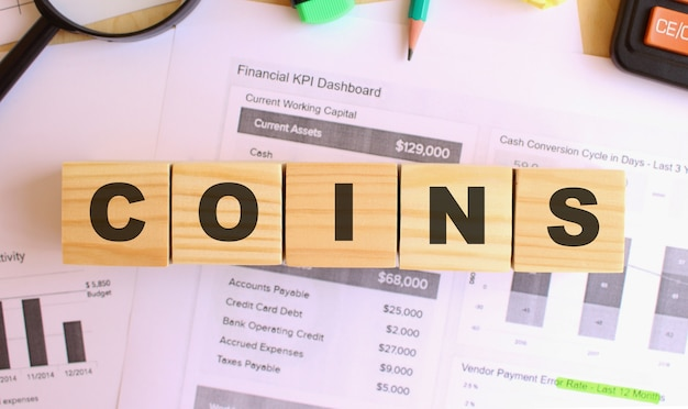 Wooden cubes with letters on the table in the office. text coins. financial concept.