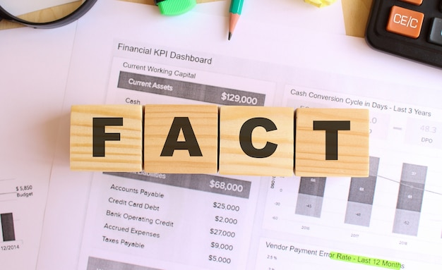 Wooden cubes with letters on the table in the office. text fact. financial concept.