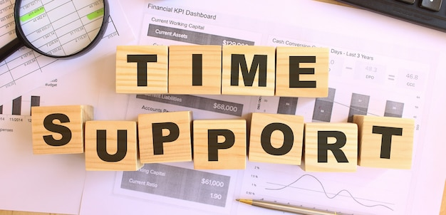 Wooden cubes with letters on the table in the office. text time support . financial concept.