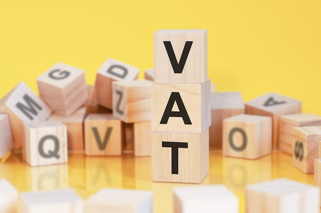 Wooden cubes with letters vat arranged in a vertical pyramid, yellow background, reflection from the surface of the table, business concept, vat - short for value added tax