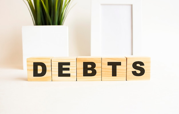 Wooden cubes with letters on a white table. the word is debts
