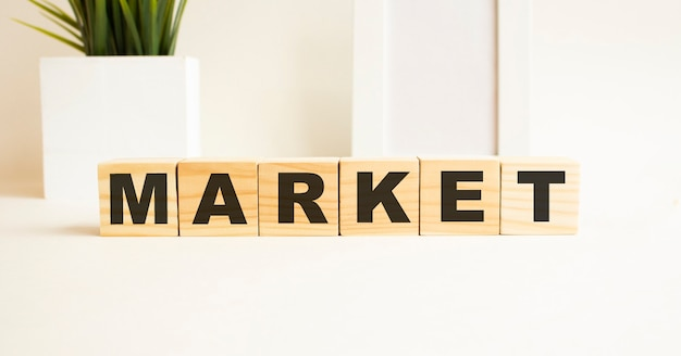 Wooden cubes with letters on a white table. the word is market
