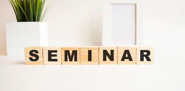 Wooden cubes with letters on a white table. the word is seminar