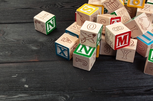 Wooden cubes with letters on wooden background