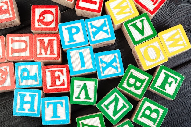Wooden cubes with letters on wooden table top view