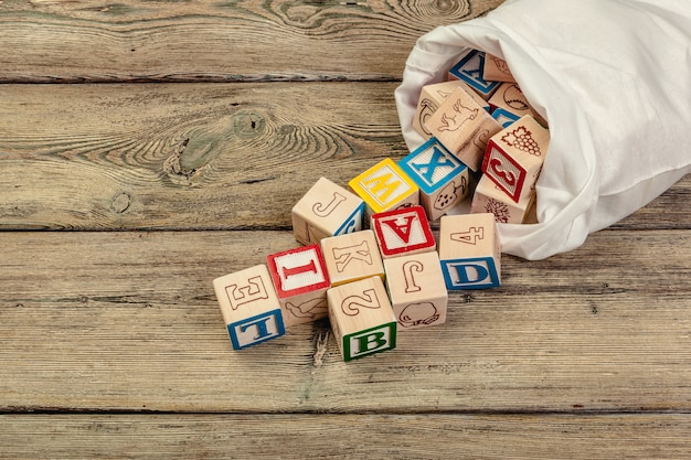 Wooden cubes with letters on wooden table