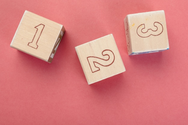 Wooden cubes with numbers on tabletop close up