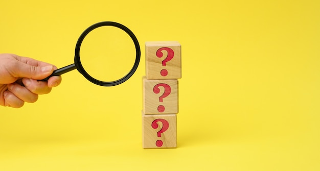 Wooden cubes with question marks and a female hand holds a magnifying glass on a yellow surface