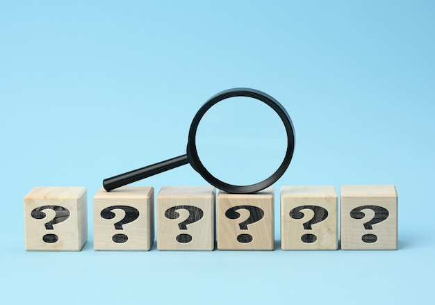 Wooden cubes with question marks and a magnifying glass on a blue background. the concept of finding answers to unknown questions, solving a problem. find information
