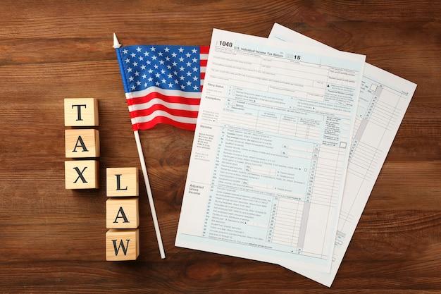 テーブルにアメリカ国旗が付いたテキストと所得税フォーム用のスペースのある木製の立方体。税法の概念