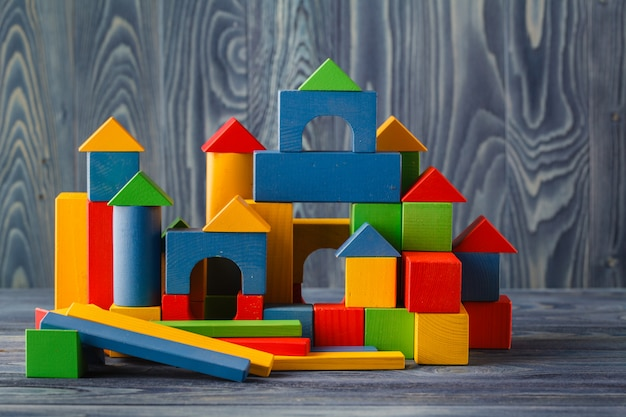 Wooden cubes with space for text and colourful castle on blue table
