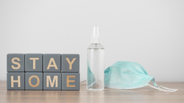 Wooden cubes with stay home and hand sanitizer next to medical mask