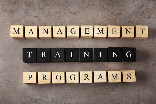 色の背景にテキスト管理トレーニングプログラムと木製の立方体